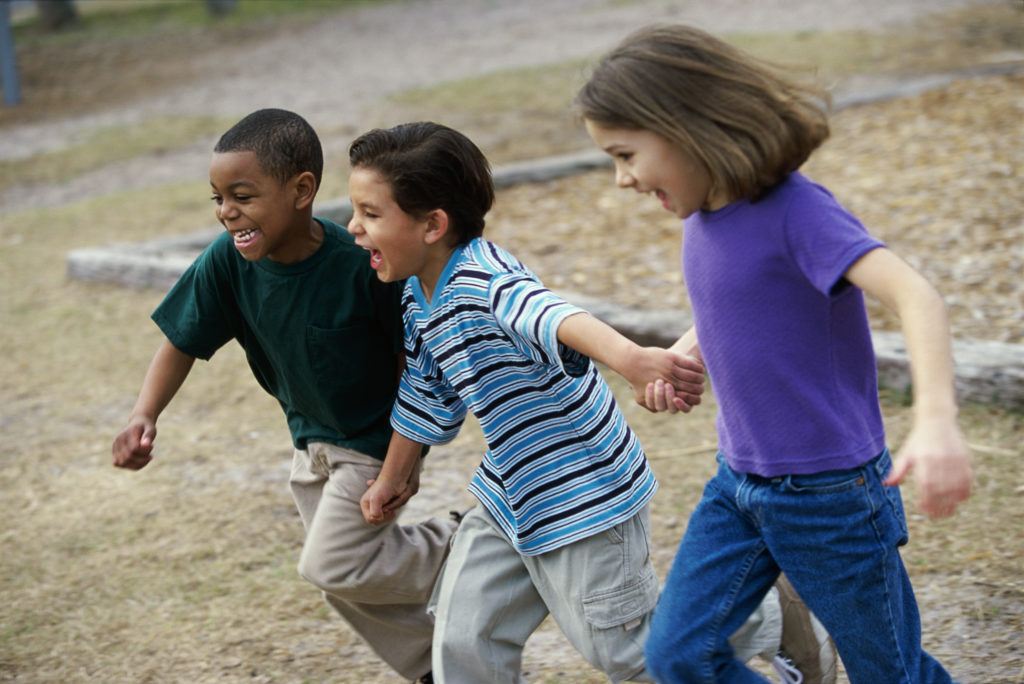 Children running on a playground holding hands