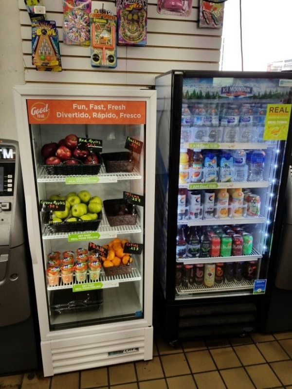 The Healthy Corner Store conversion after with a cooler of fruit and a beverage cooler full of water, seltzer, and other healthy beverages
