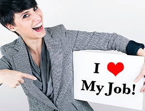 """Woman holding a sign that says, """"I love my job"""""""
